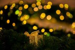 Regalo de oro hermoso adornado en el árbol de navidad borroso en el fondo del bokeh del oro - foco selectivo Foto de archivo libre de regalías