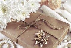 Regalo decorato con i fiori bianchi e le cose romantiche Immagine Stock