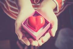Regalo del amor Regalo caluroso Una caja de regalo con un corazón rojo dentro Fotos de archivo