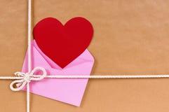 Regalo del biglietto di S. Valentino, carta rossa del cuore o etichetta del regalo, pacchetto della carta marrone Immagini Stock Libere da Diritti