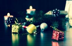 Regalo del ` s del Año Nuevo en el embalaje rojo con un arco del oro cerca de la pata de la macro del primer del árbol de navidad Imagen de archivo