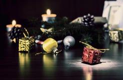 Regalo del ` s del Año Nuevo en el embalaje rojo con un arco del oro cerca de la pata de la macro del primer del árbol de navidad Fotografía de archivo