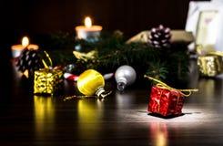 Regalo del ` s del Año Nuevo en el embalaje rojo con un arco del oro cerca de la pata de la macro del primer del árbol de navidad Imagenes de archivo