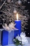 Regalo del ` s del Año Nuevo en la caja azul y la vela Fondo negro Foto de archivo libre de regalías