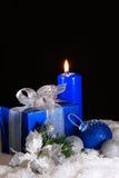 Regalo del ` s del Año Nuevo en la caja azul y la vela Fondo negro Fotos de archivo libres de regalías