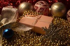 Regalo del ` s del nuovo anno fra le decorazioni di Natale Fotografia Stock Libera da Diritti
