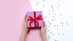 Regalo della tenuta della donna in mani Contenitore di regalo rosa Copi lo spazio fotografie stock