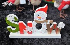 Regalo di legno del pupazzo di neve della neve di Natale decorato con i fiocchi di neve Fotografia Stock