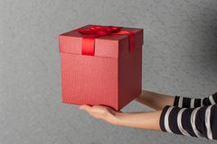 Regalo di lusso di giorno di S. Valentino in mani della donna su fondo blu Il concetto del regalo di festa Immagine Stock