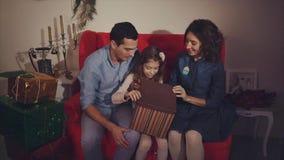 Regalo di Natale aperto della famiglia felice, genitori colpiti Concetto del regalo video d archivio