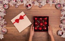 Regalo di Natale di apertura del bambino con le bagattelle rosse Immagini Stock