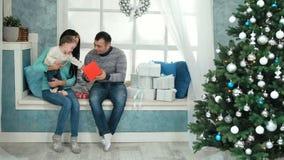 Regalo di Natale di apertura della famiglia davanti all'albero video d archivio
