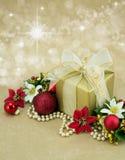 Regalo di Natale con i fiori e le bagattelle rosse. Fotografia Stock
