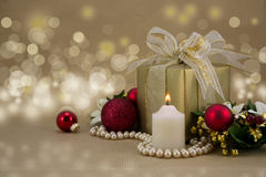 Regalo di Natale con la candela e le bagattelle rosse. Immagine Stock