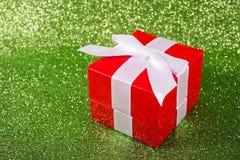 Regalo di Natale contro uno scintillio magico brillante Immagini Stock Libere da Diritti