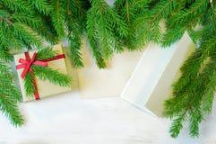 Regalo di Natale decorato con il ramoscello dell'albero di Natale, busta e Fotografia Stock Libera da Diritti