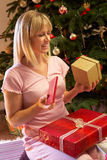 Regalo di Natale di apertura della donna davanti all'albero Fotografie Stock