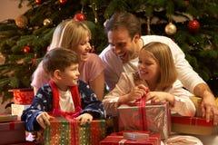Regalo di Natale di apertura della famiglia davanti all'albero Fotografia Stock