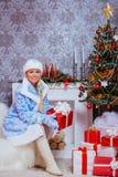 Regalo di Natale nubile felice della tenuta della ragazza al camino fotografia stock libera da diritti
