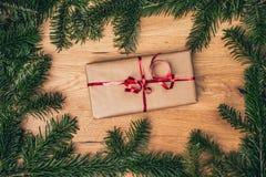 Regalo di Natale sul bordo di legno con l'albero di abete, campane rosse immagine stock