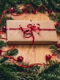 Regalo di Natale sul bordo di legno con l'albero di abete, campane rosse fotografia stock libera da diritti