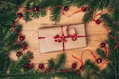 Regalo di Natale sul bordo di legno con l'albero di abete, campane rosse immagini stock libere da diritti