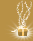 Regalo dorato di Natale con i raggi luminosi Fotografie Stock
