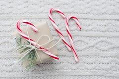 Regalo e bastoncini di zucchero su fondo tricottato bianco Fotografie Stock