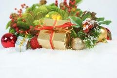 Regalo e decorazioni di Natale accoccolati in neve Fotografie Stock