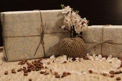 Regalo en la caja y una rama de un árbol floreciente Foto de archivo