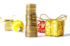 Regalo en una caja del oro con un arco en una pila de monedas de oro en un fondo de otros regalos aislados en un blanco Fotos de archivo libres de regalías