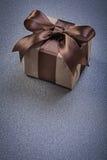 Regalo encajonado con la cinta marrón en conce gris de las celebraciones del fondo fotografía de archivo libre de regalías