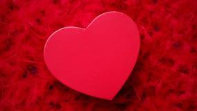Regalo encajonado en forma de corazón, colocado en fondo rojo de las plumas