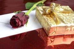 Regalo envuelto en papel del oro, rosa del rojo y un sobre en blanco foto de archivo