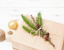 Regalo envuelto en papel normal con una rama del piel-árbol y las bolas de la Navidad Imagen de archivo