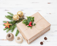 Regalo envuelto en papel normal con una rama del piel-árbol y las bolas de la Navidad Fotografía de archivo