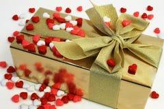Regalo envuelto rodeado con los caramelos en forma de corazón Imagen de archivo