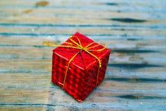 Regalo envuelto rojo en el contexto rústico Fotografía de archivo libre de regalías