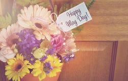Regalo feliz del primero de mayo de flores en puerta Foto de archivo