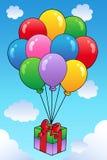 Regalo flotante con los globos de la historieta Foto de archivo libre de regalías