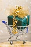 Regalo grande de la Navidad en carro de compras Imagen de archivo