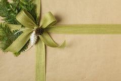Regalo hermoso de la Navidad envuelto en papel de embalaje reciclado con las decoraciones botánicas naturales fotografía de archivo
