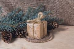 Regalo nei retro stili ed albero di Natale con i coni Fotografia Stock