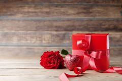 Regalo o actual caja, corazón y flor color de rosa en la tabla rústica de madera Tarjeta de felicitación del día de la madre o de imagen de archivo