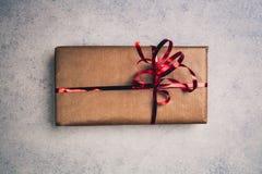 Regalo o presente in scatola di carta marrone con il nastro rosso, sopra la vista immagini stock