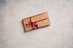 Regalo o presente in scatola di carta marrone con il nastro rosso, sopra la vista fotografia stock libera da diritti