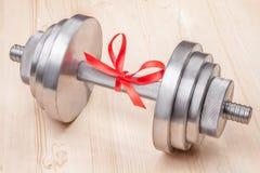 Regalo - pesa de gimnasia atada con la cinta roja en el escritorio de madera Foto de archivo