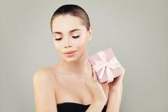 Regalo piacevole della tenuta della donna con il nastro rosa su Gray Fotografie Stock