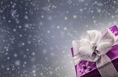 Regalo porpora del biglietto di S. Valentino o di Natale con il fondo d'argento di gray dell'estratto del nastro Immagine Stock