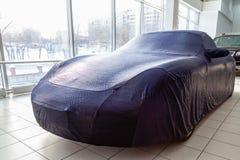 Regalo preparado en la sala de exposición, un coche de deportes cubierto con un toldo azul de la cubierta protectora para los coc foto de archivo